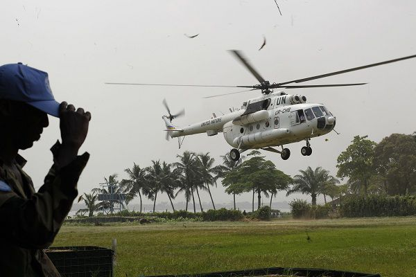 A Senegalese United Nations peacekeeper holds his cap against the wind and debris raised by a landing U.N. helicopter, at the Golf Hotel in Abidjan, Ivory Coast, Tuesday, Jan. 4, 2011. Alassane Ouattara, recognized internationally as Ivory Coast's elected leader, is attempting to govern from a hotel in Abidjan where he and his staff are barricaded behind sandbags and giant coils of razor wire. In recent weeks, getting supplies to the Golf Hotel has become increasingly difficult, and the U.N. started running daily helicopter flights that land on the hotel's lawn ferrying cartons of vegetables and tins of powdered milk.(AP Photo/Rebecca Blackwell)