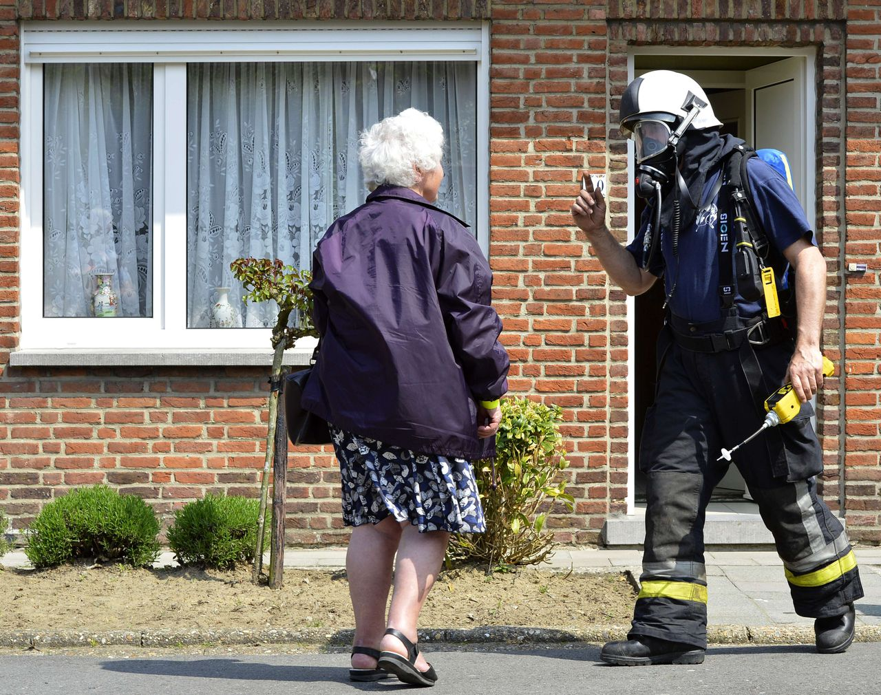 A woman talks to a toxic specialist to check if her house is free from toxins, in Wetteren, on May 6, 2013. On Saturday night a freight train derailed and exploded on a track near Schellebelle (part of Wichelen, Wetteren). The train contained the chemical product acrylonitrile, a toxic and inflammable fluid that can cause breathing problems. Emergency services evacuated some 500 residents. One local resident died and 49 persons were brought to hospital. AFP PHOTO/ BENOIT DOPPAGNE
