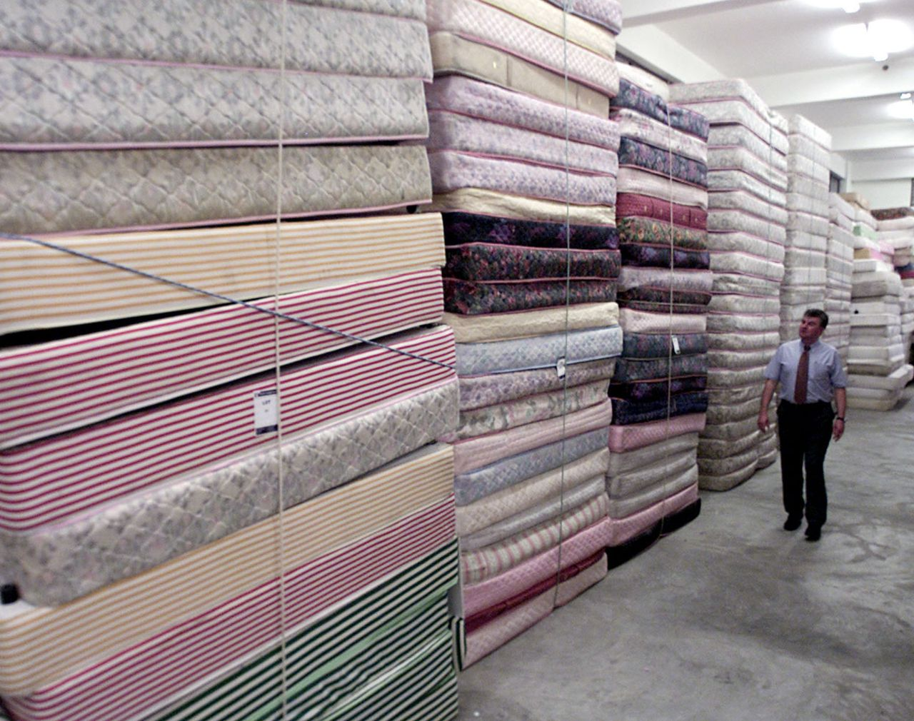Man bekijkt wat matrassen. A man looks at mattresses put up for auction in Brunei's capital Bandar Seri Bagawan August 9, 2001. The tiny-oil rich sultanate begins a multi-million dollar auction on Saturday of assets that once belonged to Prince Jefri, its ruler's estranged younger brother. ZH/JD