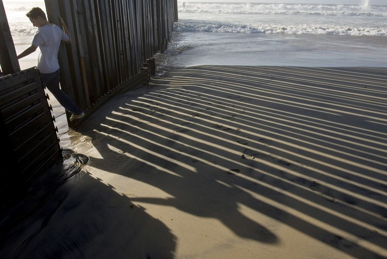 A man jumps from the U.S. back into Mexico through a gap in the border fence between the two countries where it extends into the Pacific Ocean, after a storm that hit the region caused damage to the fence, in San Diego January 3, 2006. The Mexican government has bitterly criticized a bill, approved by the U.S. House of Representatives last month, which would make illegal entry a felony, involve the military and local police in stopping illegal immigrants and result in the construction of more border fences. REUTERS/Fred Greaves Gat in de muur. Verenigde Staten en Mexico. Grens
