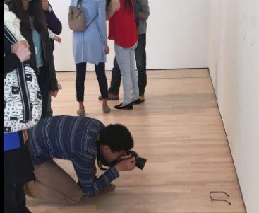 Een museumbezoeker fotografeert het nepkunstwerk.