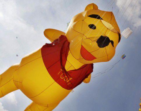 Een enorme Winnie de Poeh hangt boven het strand van Scheveningen tijdens een internationaal vliegerfeest.