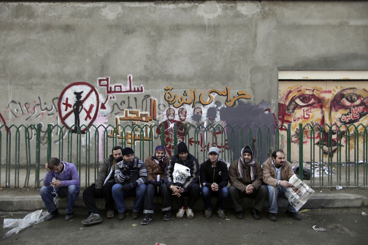 """Egyptian protesters sit on a curb beneath revolutionary graffiti in Tahrir Square as thousands gather to mark the one year anniversary of the uprising that ousted President Hosni Mubarak in Cairo, Egypt, Wednesday, Jan. 25, 2012. The yellow Arabic writing above them reads, """"thief of the revolution"""".(AP Photo/Muhammed Muheisen)"""