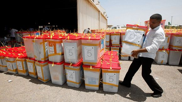 Caption: A man carries ballot boxes after collecting them from different polling stations, as the High Election Commission prepares for the final count, at a Maatiga airport shed in Tripoli July 8, 2012. Libyans, relieved that their first free national election in 60 years had survived violence and protests, celebrated the chance to draw a line under Muammar Gaddafi's dictatorship and forge a brighter future for their North African country. REUTERS/Ismail Zitouny (LIBYA - Tags: POLITICS ELECTIONS)