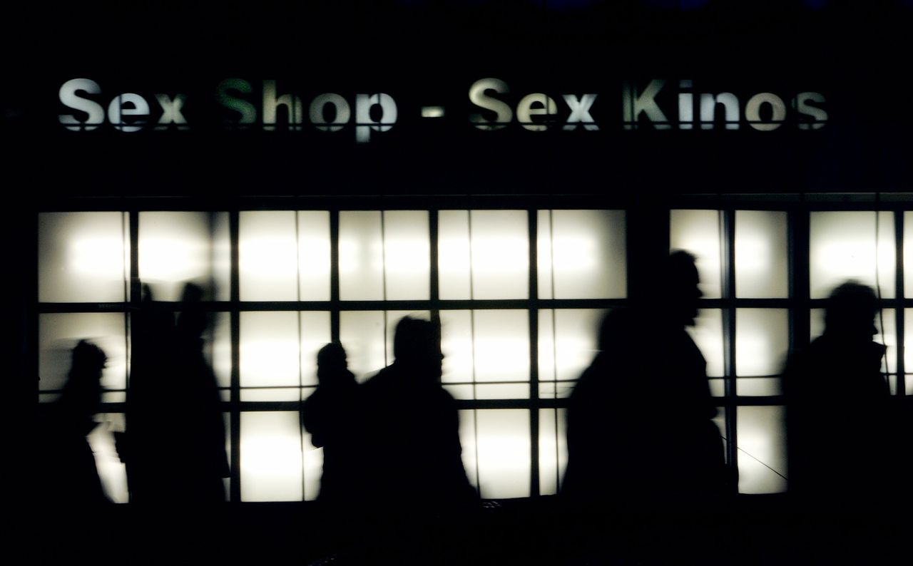 People pass an erotic store in the famous red light district 'Reeperbahn' in the northern German town of Hamburg in this photograph taken on March 3, 2006.The combination of riveting World Cup soccer matches and crowds of beer-swilling males means hefty profits for Germany's sex industry, which will deploy an army of prostitutes to satisfy the needs of libidinous fans. Some 1 million foreign visitors are expected to flood into Germany to watch the 2006 World Cup from June 9 to July 9 and many in the horizontal economy expect large numbers of male spectators to wind down after a match in the arms of a prostitute or in the red light districts of the 12 host cities. Picture taken March 3, 2006. To accompany feature GERMANY PROSTITUTION WCUP REUTERS/Christian Charisius De Reeperbahn in Hamburg, een van de steden waar WK-wedstrijden worden gespeeld.