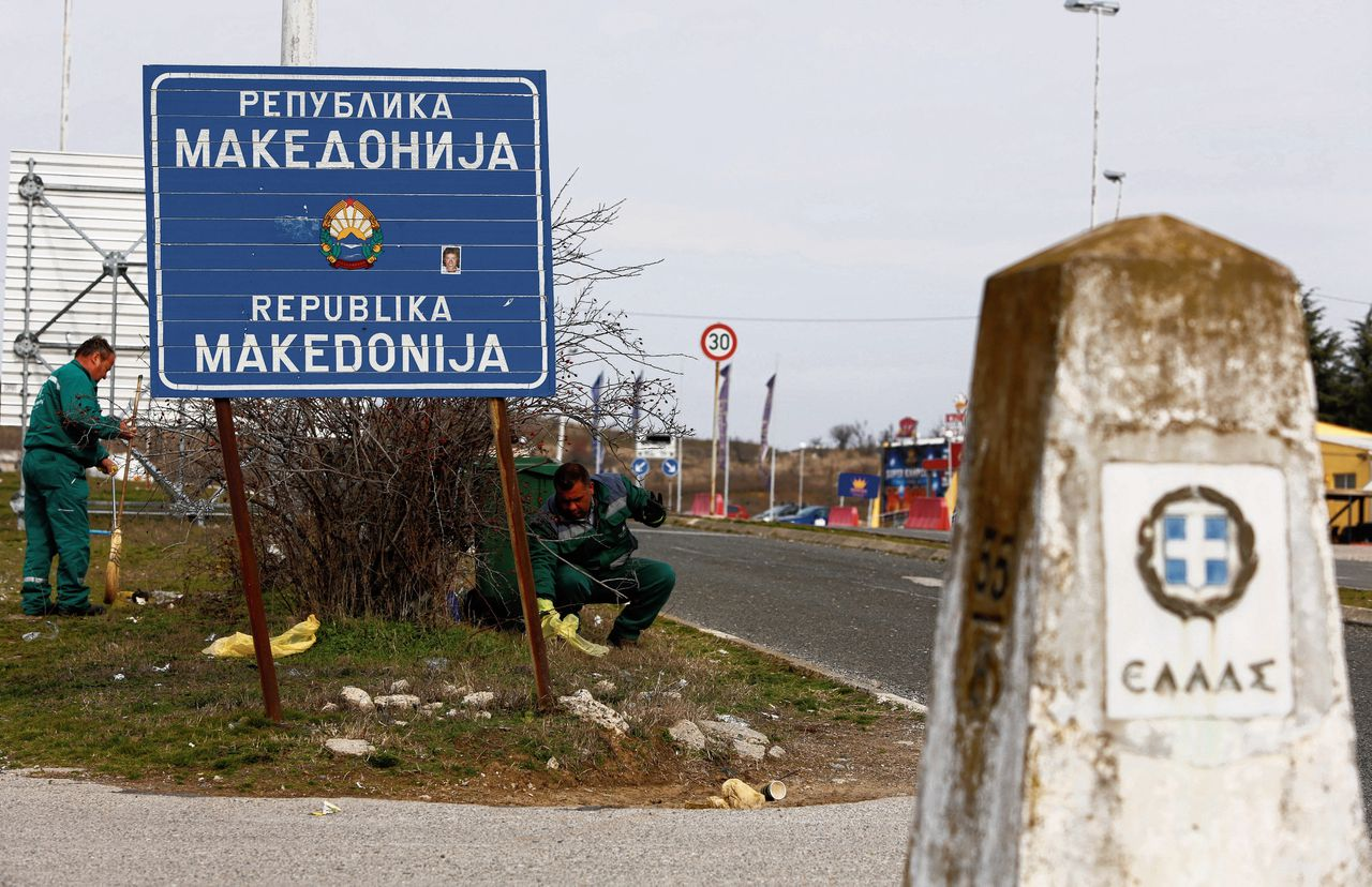 """Workers clean up near the sign at the border between Macedonia and Greece, near Gevgelija, February 11, 2019. Picture taken February 11, 2019. A sign reads: """"Republic of Macedonia"""". REUTERS/Ognen Teofilovski"""