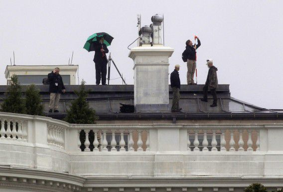 A crew works atop the White House on the side that was hit by bullets last week in Washington November 16, 2011. Police arrested a 21-year old man on Wednesday suspected of shooting at the White House last week, after federal agents found two bullets that had hit the mansion, including one that struck a window. REUTERS/Kevin Lamarque (UNITED STATES - Tags: CRIME LAW POLITICS)