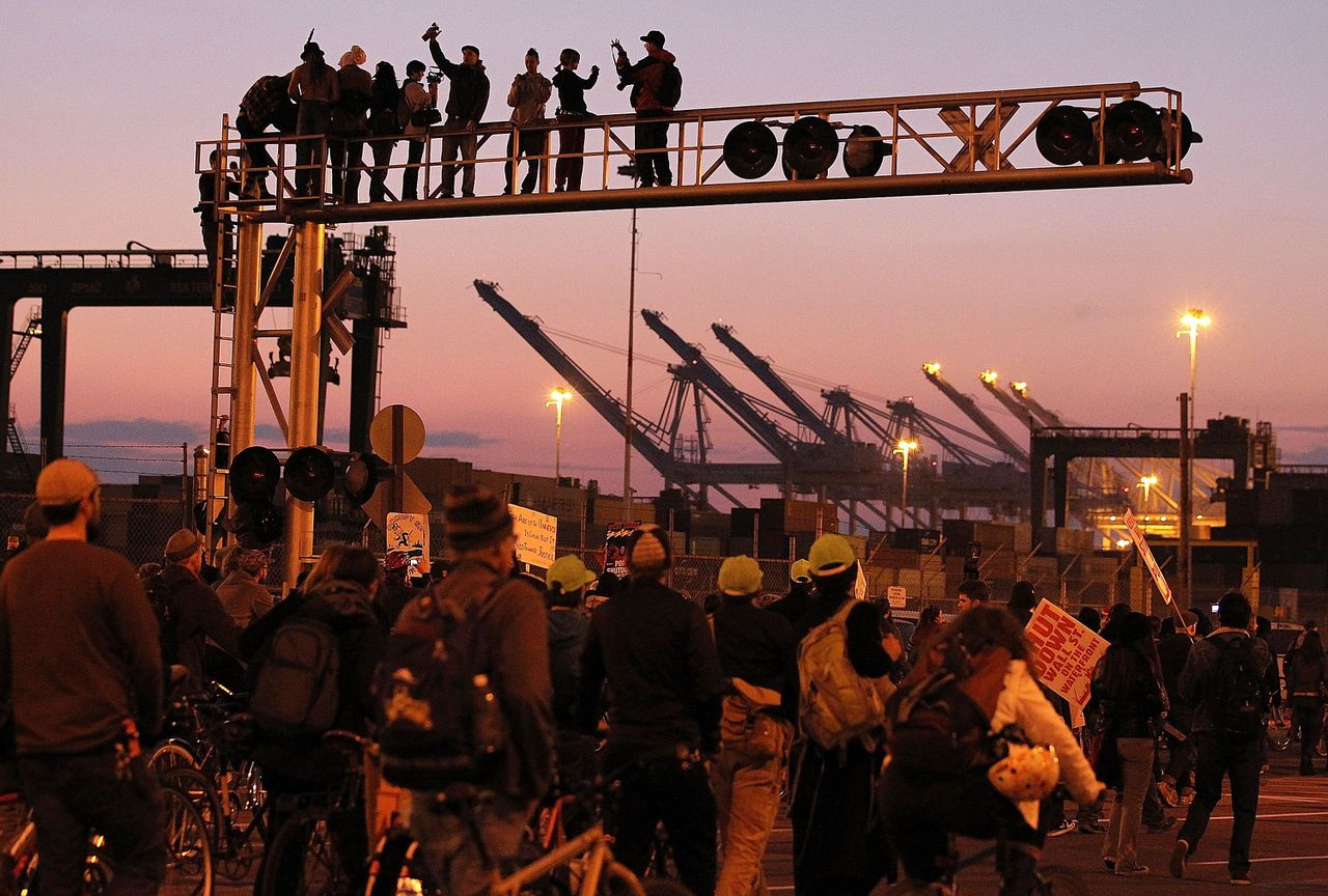 OAKLAND, CA - DECEMBER 12: Occupy protestors stand on a railroad crossing during a march at the Port of Oakland on December 12, 2011 in Oakland, California. Following a general strike coordinated by Occupy Oakland that closed the Port of Oakland on November 2, Occupy Wall Street protestors are attempting to shut down all West Coast ports in Los Angeles, San Diego, Oakland, Portland, Seattle and Tacoma. Justin Sullivan/Getty Images/AFP == FOR NEWSPAPERS, INTERNET, TELCOS & TELEVISION USE ONLY ==