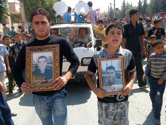 "In this citizen journalism image made on a mobile phone and provided by Shaam News Network, anti-Syrian President Bashar Assad protesters hold portraits for their dead relatives killed in recent violence, as they march during a demonstration against the Syrian regime, at Maaret Harma village, in Edlib province, Syria, on Friday Sept. 9, 2011. Syrian security forces ""forcibly removed"" patients from a hospital and prevented doctors from reaching the wounded during a military siege in the restive central city of Homs this week, a leading human rights group said. (AP Photo/Shaam News Network) EDITORIAL USE ONLY, NO SALES, THE ASSOCIATED PRESS IS UNABLE TO INDEPENDENTLY VERIFY THE AUTHENTICITY, CONTENT, LOCATION OR DATE OF THIS HANDOUT PHOTO"
