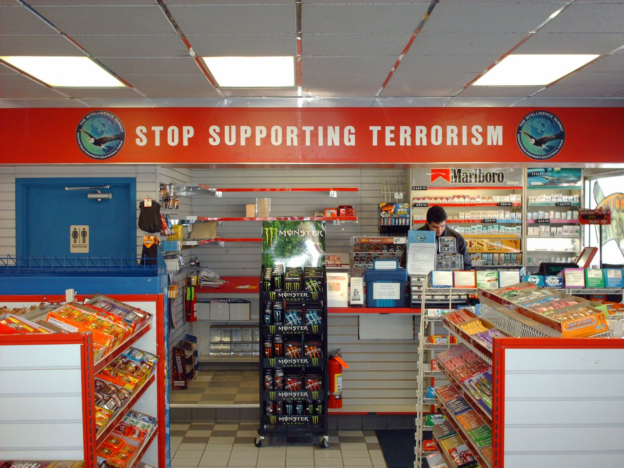 """Amerikanen willen kunnen tanken in de wetenschap dat hun geld niet in het Midden-Oosten terechtkomt. Foto AFP TO GO WITH AFP STORY AFPLIFESTYLE-US-MIDEAST-OIL-PROTEST This undated handout photo received 15 February 2007 show a """"terror-free oil"""" sign inside a gas station convenience store in Ohama, Nebraska. The first """"terror-free"""" gas station was inaugurated this week in the central US state of Nebraska with the aim of sending a message to Middle Eastern countries thought to sponsor terrorism. The station in the city of Omaha greets customers with large """"terror-free"""" signs and the pumps proudly proclaim that the oil being drawn is """"terror-free premium"""" or """"terror-free super"""". Messages are also plastered inside the convenience store at the station and at other locations to drive home the message that the station only uses oil from Canada and the United States and supports the war on terror. AFP PHOTO/TERROR-FREE OIL/HO/=GETTY OUT="""