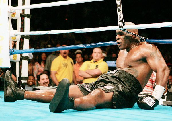 Mike Tyson sits on the canvas at the end of round six after Ireland's Kevin McBride pushed him to the mat during their heavyweight boxing fight at MCI Center in Washington June 11, 2005. Tyson's corner asked the referee to stop the fight, giving McBride the win. REUTERS/Gary Hershorn PICTURES OF THE YEAR 2005