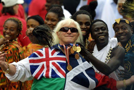 (FILES) In this file picture taken on June 4, 2002 Jimmy Savile, a television and radio celeberity joins in with people representing Commonwealth countries wearing their tradional dress crowd into the forecourt of Buckingham Palace during the Golden Jubilee celebrations in London. Prime Minister David Cameron hinted on October 9, 2012 that the late Jimmy Savile, who was one of Britain's biggest TV stars, could be stripped of his knighthood after a string of sexual abuse claims. AFP PHOTO/ ADRIAN DENNIS/FILES