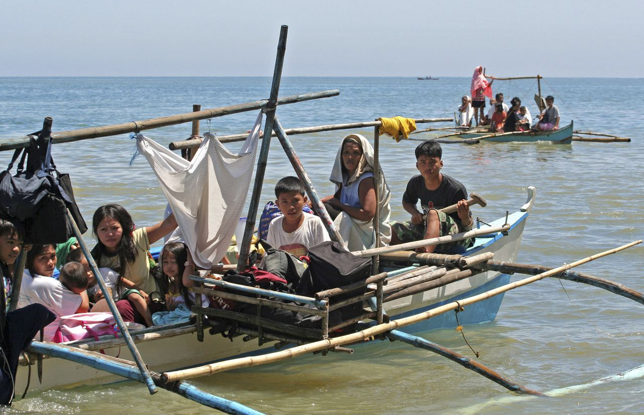 Bewoners van Kauswagan ontvluchtten in bangka?s, traditionele Filippijnse bootjes, de gewelddadigheden in hun dorp in augustus vorig jaar. (Foto Reuters) Residents ride a boat with their belongings as they flee Kauswagan town, Lanao del Norte southern Philippines August 18, 2008. The Philippines ordered troops to clear Muslim guerrillas out of several towns on the southern island of Mindanao on Monday after they attacked soldiers, burnt houses and forced hundreds of people to flee. REUTERS/Stringer (PHILIPPINES)