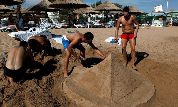 "Caption: FILE - In this Wednesday, Dec. 8, 2010 file photo, tourists build a sand pyramid at a closed beach in the Red Sea resort of , Egypt. Some newly empowered Islamists have a message for foreign tourists: welcome to Egypt, but no booze, bikinis or mixed bathing at beaches, please. The vision of turning the country into a sin-free vacation spot could spell doom for a pillar of the economy already battered by political unrest. ""Tourists don't need to drink alcohol when they come to Egypt; they have plenty at home,"" one Muslim Brotherhood candidate told a cheering crowd. (AP Photo/Nasser Nasser, File)"