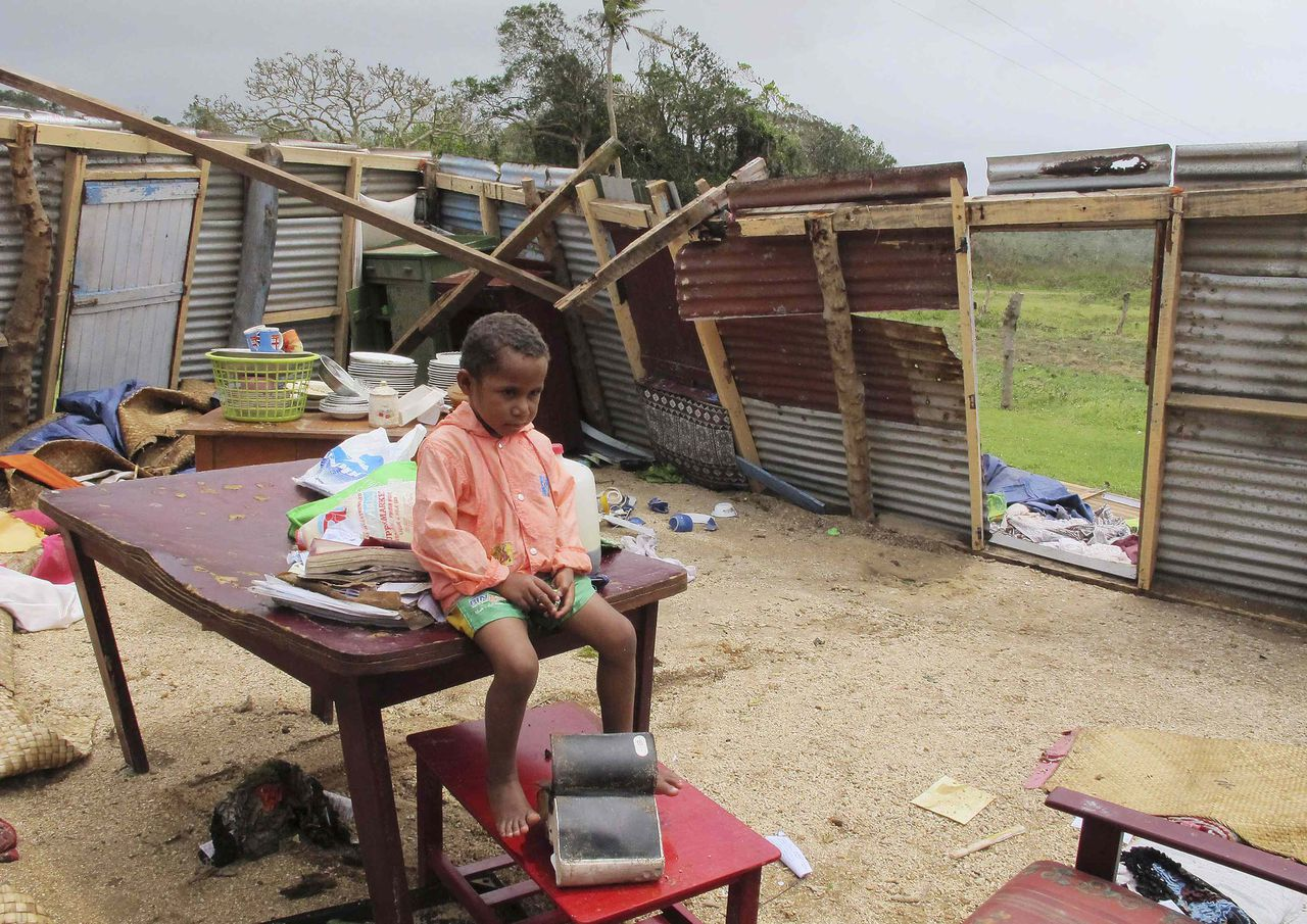 A boy sits on a table at the Christian Mission Fellowship church, which lost its roof during Tropical Cyclone Evan, in Malomalo December 18, 2012. More than 8,000 people, including foreign tourists, were evacuated to emergency shelters as Fiji was battered by a severe tropical cyclone, with winds topping 230kmh (140 mph) and floods damaging homes and resorts. REUTERS/Tertius Pickard (FIJI - Tags: DISASTER ENVIRONMENT)
