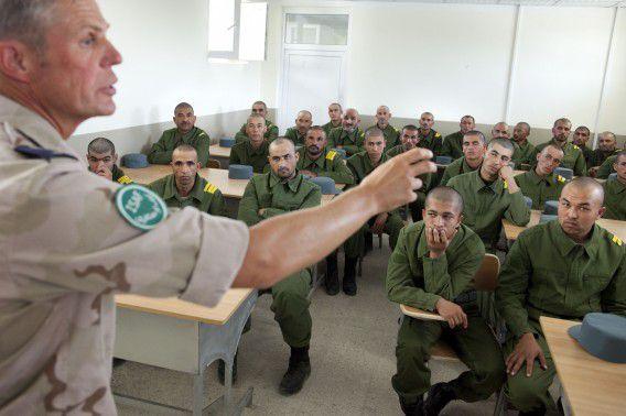 Dertig popelende Afghaanse politiemannen beginnen onder leiding van marechaussee Ron Stobbelaar aan de achtweekse opleiding waarin ze onder meer leren fouilleren, schieten en lezen. Foto Jo'l van Houdt