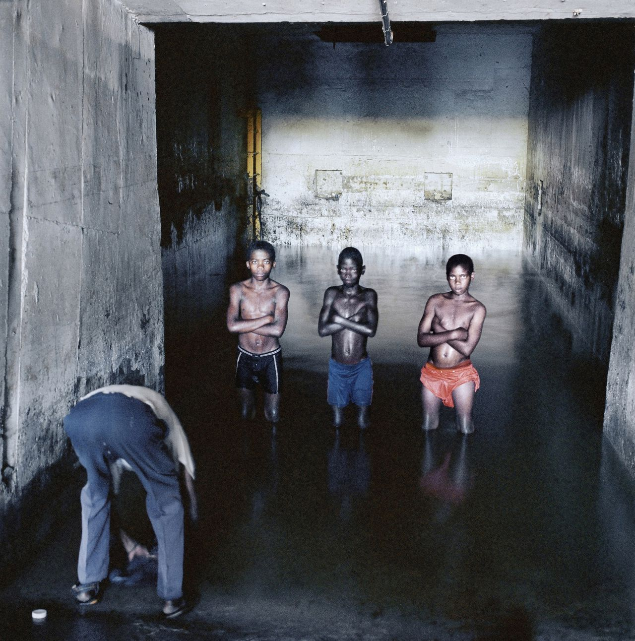 Fernando Augusto Luta washes his clothes while Augusto Mokinda (13), Ze Jano (12) an Ze Ndala (10) pose for a photograph in the water in which they swim in a mineshaft of the Pomfret Blue Asbestos Mine, Pomfret, North-West Province, 25 December 2002.