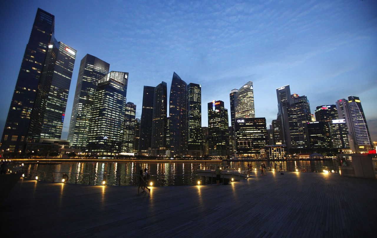 People walk past the skyline of the Marina Bay central business district in Singapore in this April 26, 2013 file photograph. Banks have a new buzzword to describe their strategy in Asia: diplomacy. Stung by regulatory probes into allegations ranging from the hiring of the offspring of senior state officials in China to rate manipulation in Singapore, and grappling with reams of new rules brought in after the global financial crisis, firms are going on a charm offensive with the region's regulators and governments. REUTERS/Edgar Su/Files (SINGAPORE - Tags: CITYSCAPE BUSINESS)
