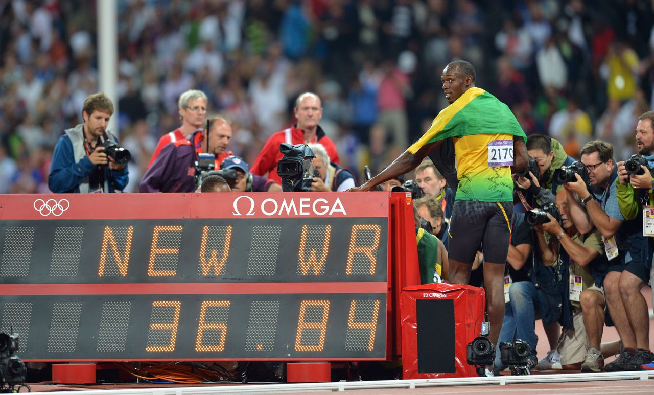 Jamaica's Usain Bolt poses with the new world record in the men's 4X100 relay final at the athletics event of the London 2012 Olympic Games on August 11, 2012 in London. AFP PHOTO / JOHANNES EISELE