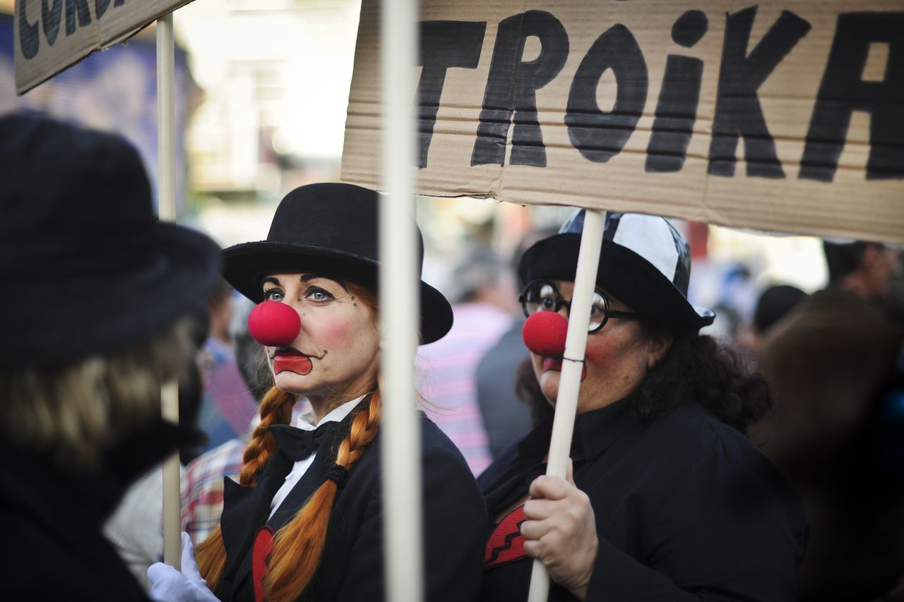 "Two women dressed as clowns hold a placard reading ""No troika"" as they gather at Espanha Square in Lisbon on October 13, 2012, to protest, with several concerts and other artistic expressions, against the Portuguese government's austerity measures. AFP PHOTO/ PATRICIA DE MELO MOREIRA"