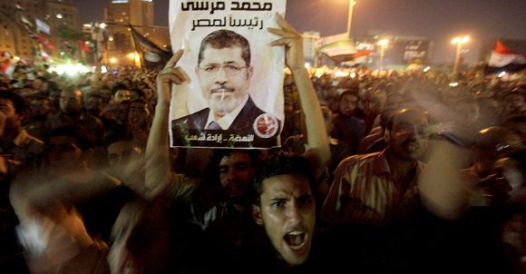 Caption: A supporter raises a photo of the Egypt's Islamist President Mohamed Mursi during the celebration of his decision on the dismissal of former defence minister and Field Marshall Hussein Tantawi, in Tahrir Square in Cairo August 13, 2012 .REUTER/Mohamed Abd El Ghany (EGYPT - Tags: POLITICS CIVIL UNREST)