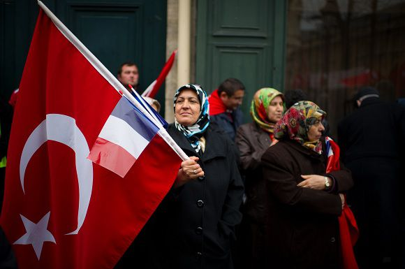 TOPSHOTS A woman holding the Turkish and French flags takes part in a rally next to the French National Assembly on December 22, 2011 in Paris as the French parliament is today expected to approve the bill, which would see anyone in France who publicly denies the 1915 Armenian genocide face a year in jail and a fine of 45,000 euros ($58,000) today and is expected to approve it. Turkey has piled pressure on France to drop the law ahead of the vote, with President Abdullah Gul and a Turkish delegation to Paris on Tuesday warning its adoption will spark a diplomatic crisis and have economic consequences. AFP PHOTO / MARTIN BUREAU
