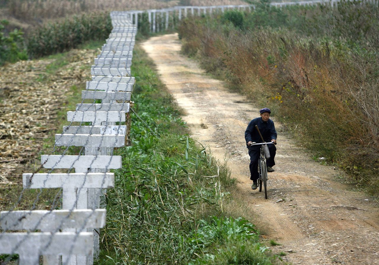 Verslaggeefster Lisa Ling reist door N-Korea. National Geographic, 22.00-23.00u. A Chinese farmer rides a bicycle beside the fence along a dam, which borders China and North Korea, in the Chinese border city of Dandong, 16 October 2006. China erected a barbed-wire fence along part of its border with North Korea shortly after the communist country conducted its first nuclear test a week ago. The aim was to prevent an exodus of North Korean refugees from the isolated state, a South Korean newspaper said Monday. AFP PHOTO/ LIU Jin