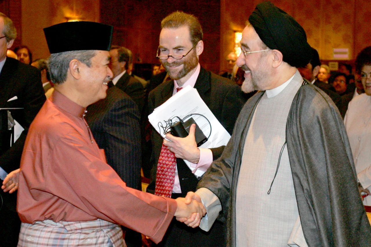 De Britse schrijver en historicus Timothy Garton Ash Malaysian Prime Minister Abdullah Ahmad Badawi (L) shakes hands with former Iranian president Mohamad Khatami (R) while Timothy Garton Ash (C), director of the European Studies Centre of St. Antony's college in Oxford University, looks on during the 'Who Speaks for Islam? Who Speaks for the West?' conference in downtown Kuala Lumpur, 10 February 2005. Religious leaders, government officials and scholars gathered in the Malaysian capital 10 February to ponder challenges facing the Muslim world, amid global bloody protests sparked by the controversial Prophet Mohammed cartoons. AFP PHOTO/TENGKU BAHAR