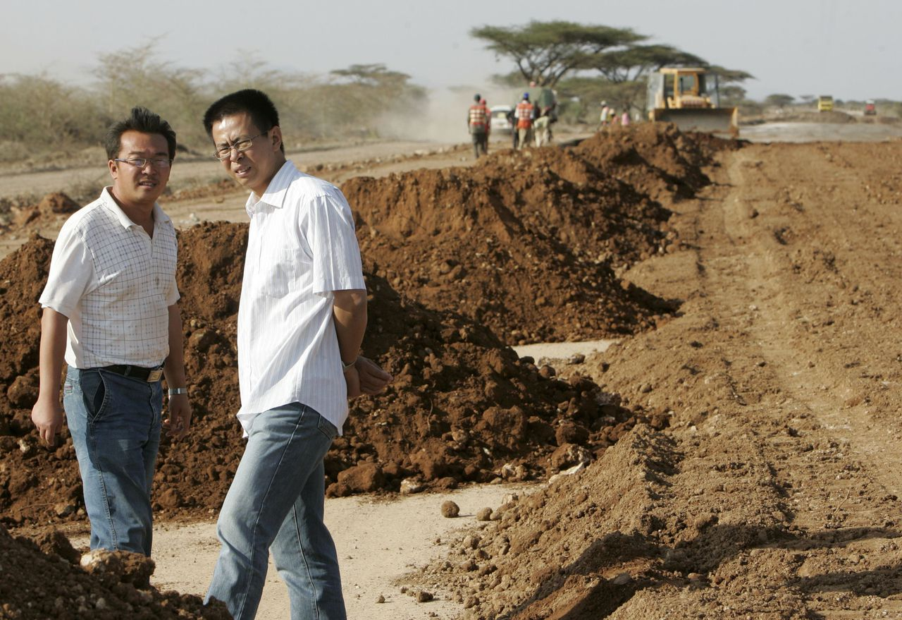 Chinese ingenieurs van het bouwbedrijf China Wuyi Company bij de aanleg van een weg bij Isiolo, ruim 300 kilometer ten noorden van de Keniaanse hoofdstad Nairobi. Foto Reuters Wu Yi Bao (R), a road construction project manager with China Wuyi Company, talks to a colleague at the site near Isiolo town, about 320 km (200 miles) north of Kenyan capital Nairobi, July 7, 2008. The road which will join Isiolo town and Ethiopia is being built by China Wuyi, a Chinese state company, and funded by African Development Bank and the Kenyan government. The project will cost 48 billion Kenya shillings ($735 million), according to the Chinese company. Picture taken on July 7, 2008. REUTERS/Antony Njuguna (KENYA)
