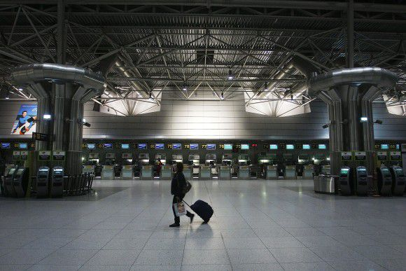 A woman walks through a deserted check-in area of the Portela international airport Wednesday, Nov. 23, 2011 in Lisbon. The two main Portuguese worker unions called for a general strike on Nov. 24 to protest government austerity measures after Portugal took a euro78 billion ($106 billion) bailout earlier this year. Air traffic controllers were some of the first workers to strike. (AP Photo/ Francisco Seco)