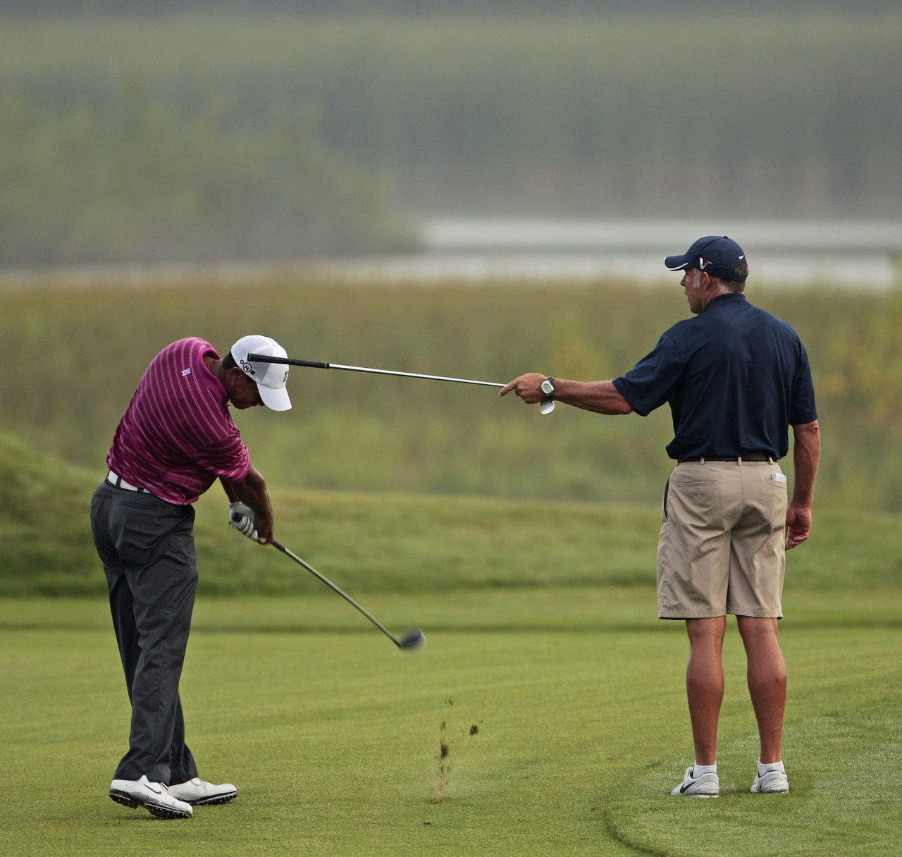 Caddie Steve Williams houdt tijdens een oefenronde met een club het hoofd van Tiger Woods stil. Foto AP Tiger Woods hits a shot as caddie Steve Williams holds a club during a practice round for the PGA Championship golf tournament Tuesday, Aug. 10, 2010, at Whistling Straits in Haven, Wis. (AP Photo/Charlie Riedel)