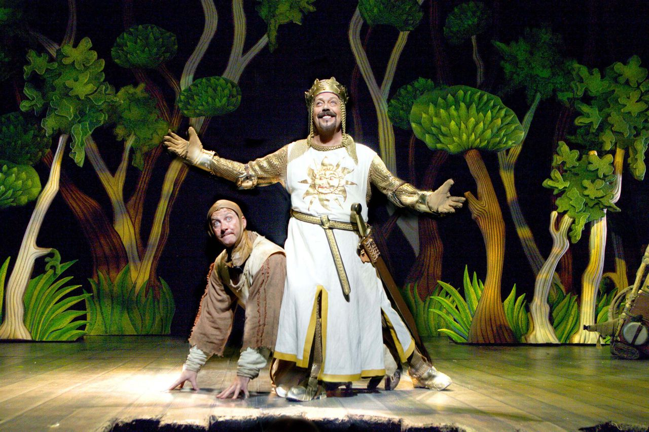 """Tim Curry as King Arthur, foreground, and David Birrell as Patsy, perform in a scene from the London production of """"Spamalot"""" in this undated handout photo. """"Spamalot,'' which received its London premiere on Monday, is stuffed full of silly parodies and lavish routines. Photographer: Catherine Ashmore via Bloomberg News"""