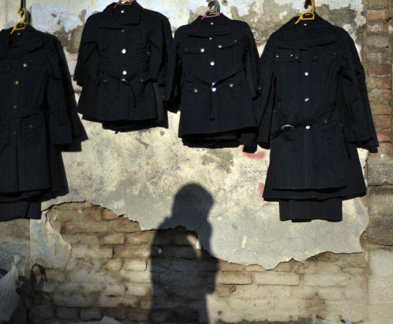 De schaduw van een Afghaanse voorbijganger op een muur waar kleren te koop hangen in Kabul, Afghanistan. Vandaag besloten NAVO-leiders dat halverwege 2013 de verantwoordelijkheid voor de veiligheid van het land zal worden overgedragen aan Afghaanse troepen.