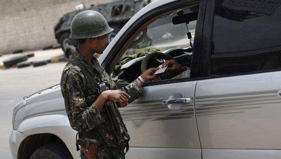 Een politieagent in Jemen inspecteert de papieren van een automobilist vanwege verhoogde veiligheidsmaatregelen na de terreurdreiging van begin augustus. Talloze ambassades trokken hun personeel terug en zijn gesloten. De Nederlandse ambassade blijft voorlopig dicht.