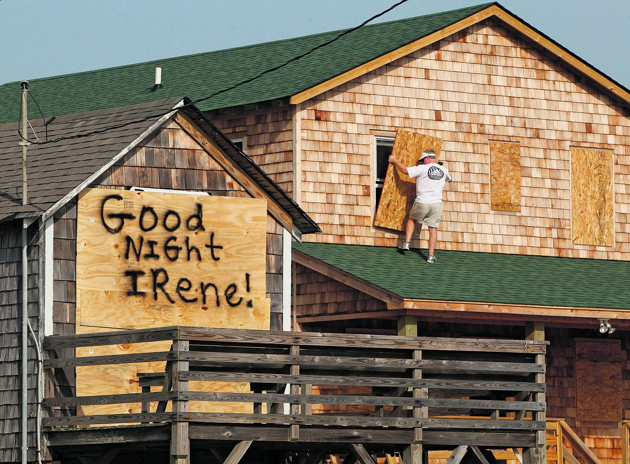 A message is left for Hurricane Irene on one house, left, as a resident boards up another in anticipation of the arrival of Hurricane Irene in Nags Head, N.C., Thursday, Aug. 25, 2011 on North Carolina's Outer Banks. (AP Photo/Charles Dharapak)