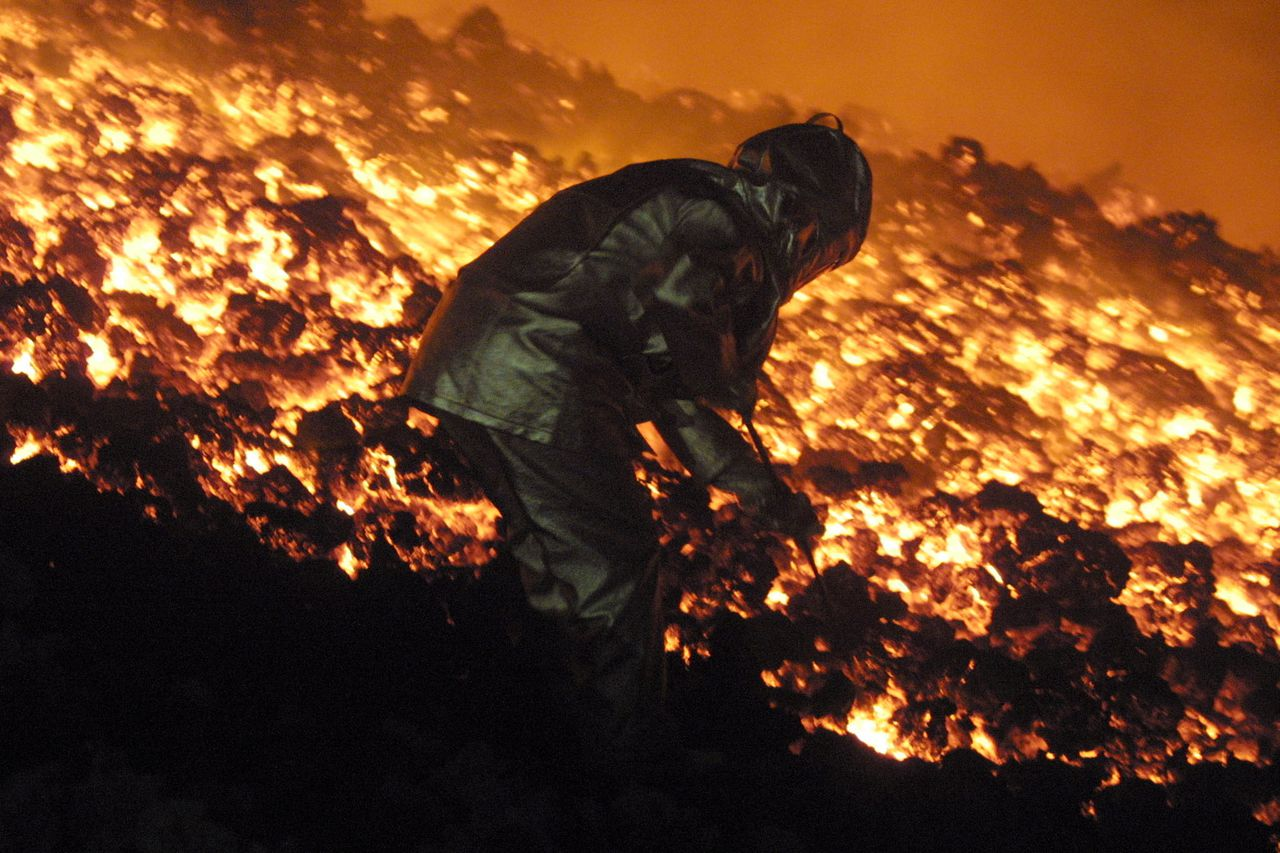 Wetenschappers volgden de uitbarsting op de flanken van de Etna in de zomer van 2001 French Charles Riviere catches a piece of lava, on the Etna volcano, east Sicily, in the night between 25 and 26 July 2001. The European most active volacano is in eruption since the 12 July 2001. Lava is about four kilometres from Nicolosi which is less than 15 kilometers from the outskirts of Catania. AFP PHOTO GABRIEL BOUYS