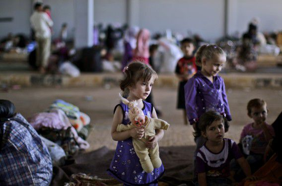 Syrian girl, Salam Farrouh, 4, who fled her home with her family due to fighting between the Syrian army and the rebels, holds her doll while playing with other children, as they and their families take refuge at the Bab Al-Salameh border crossing, in hopes of entering one of the refugee camps in Turkey, near the Syrian town of Azaz, Sunday, Aug. 26, 2012. Thousands of Syrians who have been displaced by the country's civil are struggling to find safe shelter while shelling and airstrikes by government forces continue. (AP Photo/Muhammed Muheisen)