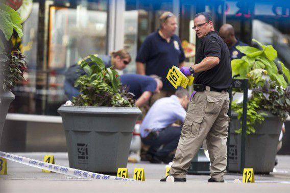 A New York Police Department officer places markers denoting spent shell casings in front of a sheet covering a body on 5th Ave after a shooting at the Empire State Building in New York August 24, 2012. REUTERS/Lucas Jackson (UNITED STATES - Tags: CRIME LAW)