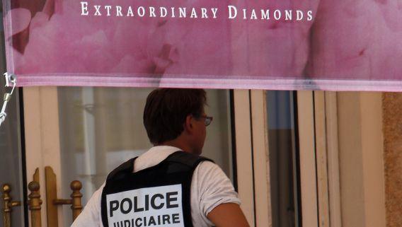 Een politieagent staat op het balkon van het hotel in Cannes waar gisteren juwelen ter waarde van meer dan 100 miljoen euro gestolen werden.