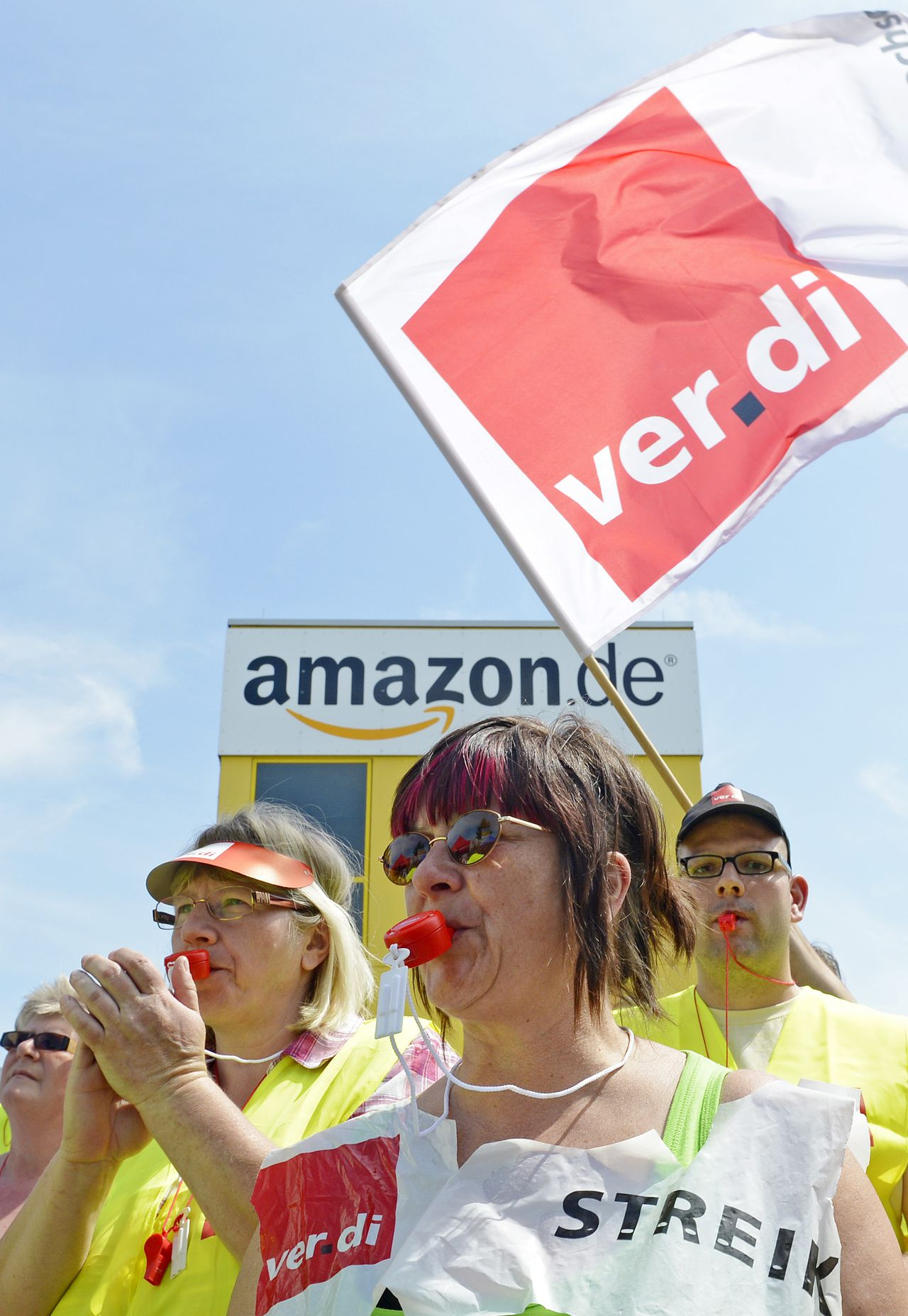 Employees of online retailer Amazon protest during their strike in front of the company's branch in Leipzig, central Germany, Monday, June 17, 2013. Union members at online retailer Amazon's German operations have begun a two-day strike to ratchet up pressure on the company over pay demands. The union says Amazon's roughly 5,300 workers at the sites receive lower wages than their peers in the online retail industry. (AP Photo/Jens Meyer)