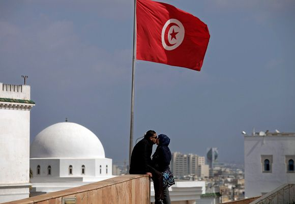 Caption: In this Friday, March 18, 2011 picture, a couple kisses underneath a Tunisian flag in Tunis, Tunisia. The Arab world's uprising against autocratic leaders began in Tunisia, after ousting Zine el-Abidine Ben Ali, their ruler of 23 years, and now the North African country is at the forefront of the transition to democracy, with elections set for the summer. But even in one of the region's most developed countries, where Islam has a largely moderate face and women enjoy more rights than their sisters elsewhere, activists fear things can still go wrong and they won't get the full-fledged democracy they want. (AP Photo/Lefteris Pitarakis)