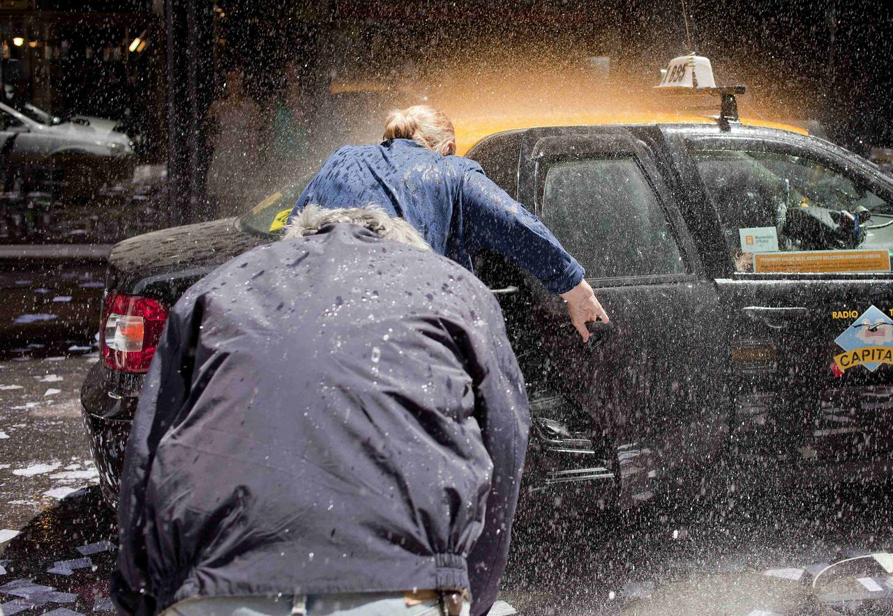 People are soaked while trying to enter a taxi in the financial district of Montevideo December 30, 2011, where workers threw water at each other to celebrate the end of the year. Workers throw water at people and discard old calendars to mark the last working day of the year on December 30. REUTERS/Pablo La Rosa (URUGUAY - Tags: SOCIETY TRANSPORT BUSINESS)