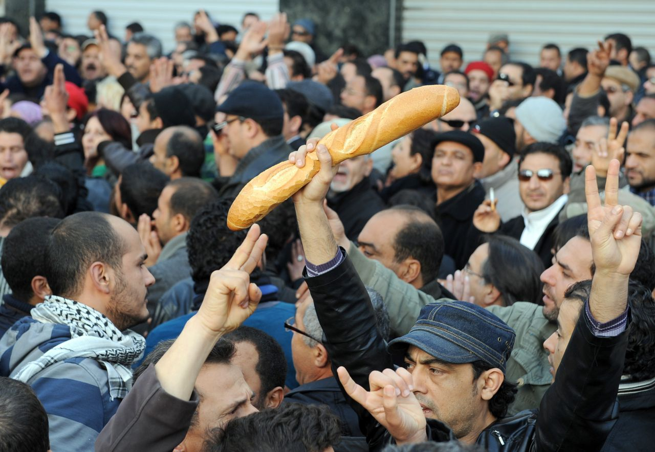 People, one of them holding bread, shout slogans to show their solidarity with the residents of Sidi Bouzid during a demonstration on December 27, 2010 in Tunis. One person was killed and others injured when Tunisia's National Guard members opened fire on angry protesters in the town of Menzel Bouzaiene over the weekend. The death came as riots and demonstrations against unemployment and poor living conditions entered their ninth day in Sidi Bouzid. Unrest scattered across the region after the suicide attempts of two young persons last week. AFP PHOTO / FETHI BELAID