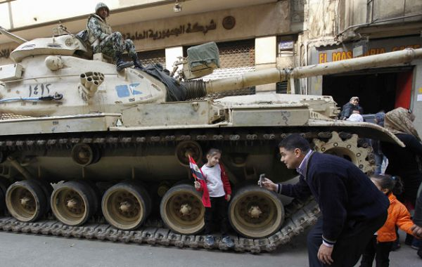 A man takes a picture of his daughter next to an Egyptian army tank in Tahrir Square in Cairo, Egypt, Monday Feb. 14, 2011. Egypt's military rulers called for an end to strikes and protests Monday as thousands of state employees, including police, demonstrated to demand better pay in a growing wave of labor unrest unleashed by the democracy uprising that ousted Hosni Mubarak's regime.(AP Photo/Hussein Malla)