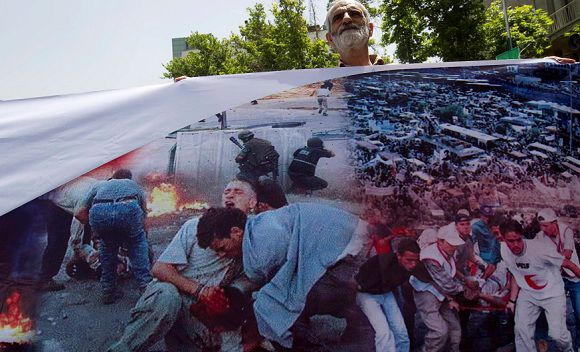 A government worker holds a banner as he participates in a rally to oppose the presence of Saudi Arabian troops in Bahrain, at Tehran's Palestine square May 23, 2011. The banner shows what the worker says are images of the crackdown on Bahraini protesters. REUTERS/Caren Firouz (IRAN - Tags: POLITICS CIVIL UNREST)