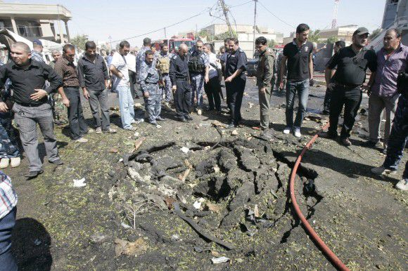 Security personnel and residents gather around a crater caused by a bomb attack in Kirkuk, 250 km (155 miles) north of Baghdad September 29, 2011. At least two people were killed and another 36 wounded when a large bomb exploded in Iraq's Kirkuk city outside a bank where police were collecting their salaries, police and hospital officials said on Thursday. REUTERS/Ako Rasheed (IRAQ - Tags: CIVIL UNREST)