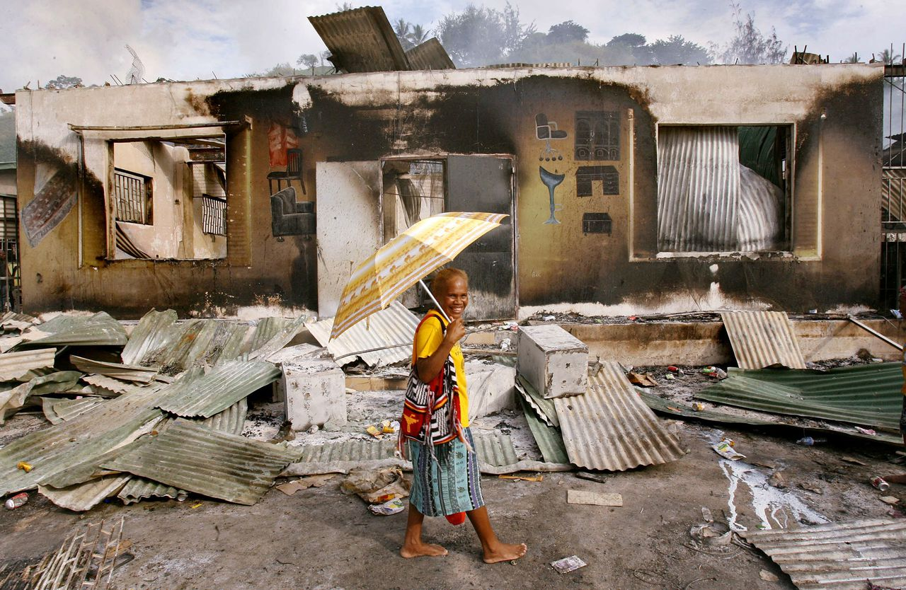 Na drie dagen van brandstichting en plunderingen hebben Australische soldaten in Honiara de rust hersteld. Premier Howard waarschuwde voor nieuwe onrust. Foto AFP A woman walks past a burnt out shop in the capital Honiara, 20 April 2006, as Australian army and police personnel arrive in the small Pacific nation to restore order after crowds burnt much of Chinatown. The city was largely quiet 20 April following two days of rioting which broke out in Honiara when Snyder Rini was elected prime minister by fellow MPs. AFP PHOTO/William WEST