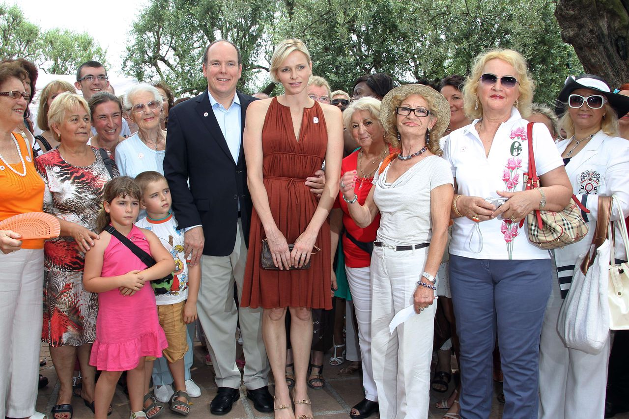 Prince Albert II of Monaco (C-L) and Princess Charlene of Monaco (C-R) pose as they attend a Red Cross picnic, on June 30, 2012 in Monaco. PHOTO / VALERY HACHE