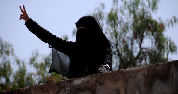 Caption: A woman flashes the victory sign on the roof of her house during a demonstration to demand the trial of Yemen's President Ali Abdullah Saleh in Sanaa November 21, 2011. Yemen's opposition said on Monday it had finalised a deal with Saleh under which he is to transfer his powers to his deputy, in a move to end 10 months of popular protests that have pushed the country to the brink of civil war. REUTERS/Mohamed al-Sayaghi (YEMEN - Tags: POLITICS CIVIL UNREST)