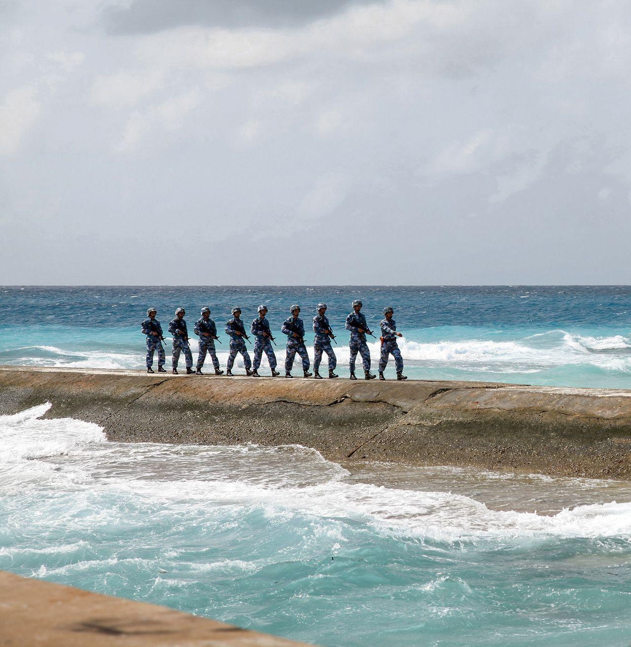 Chinese militairen patrouilleren op een van de Spratly-eilanden, door China Nansha-eilanden genoemd. Op vorige maand vrijgegeven satellietbeelden is te zien dat op een van de eilandenmogelijk een radarinstallatie is gebouwd.